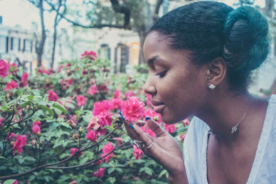 woman sniffing a pink flower