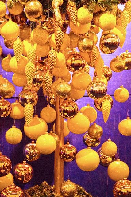 Gelbe und goldfarbige Weihnachtskugeln und Tannenzapfen
