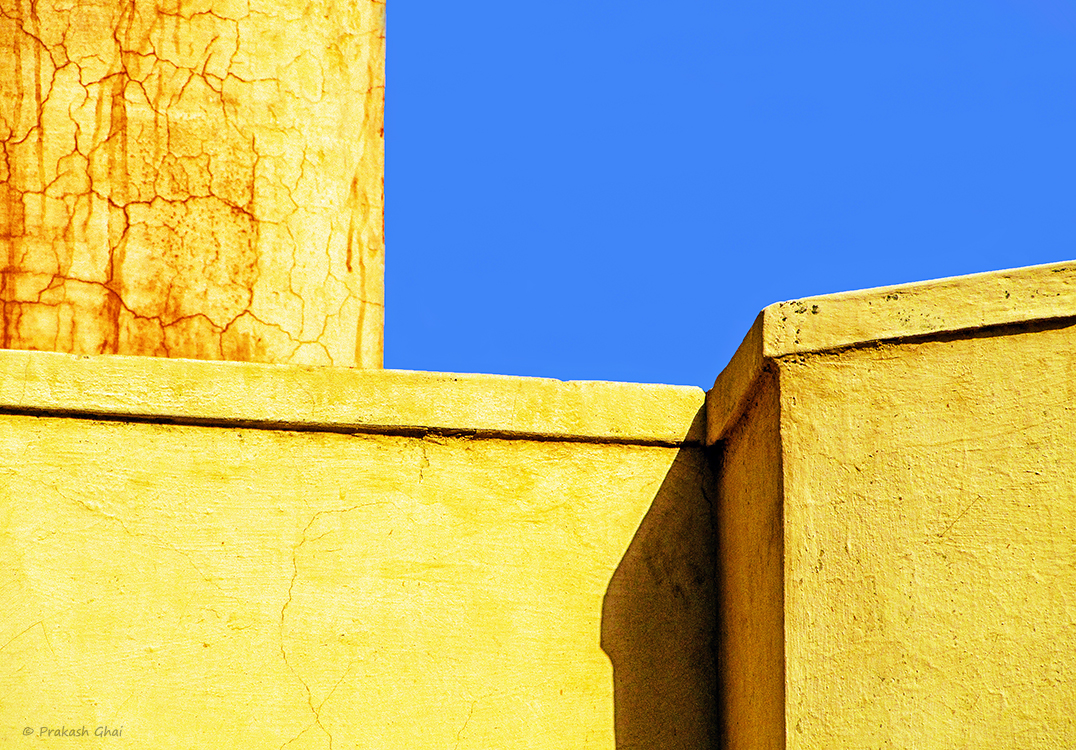 A Minimalist Photo of Yellow textured walls and blue sky