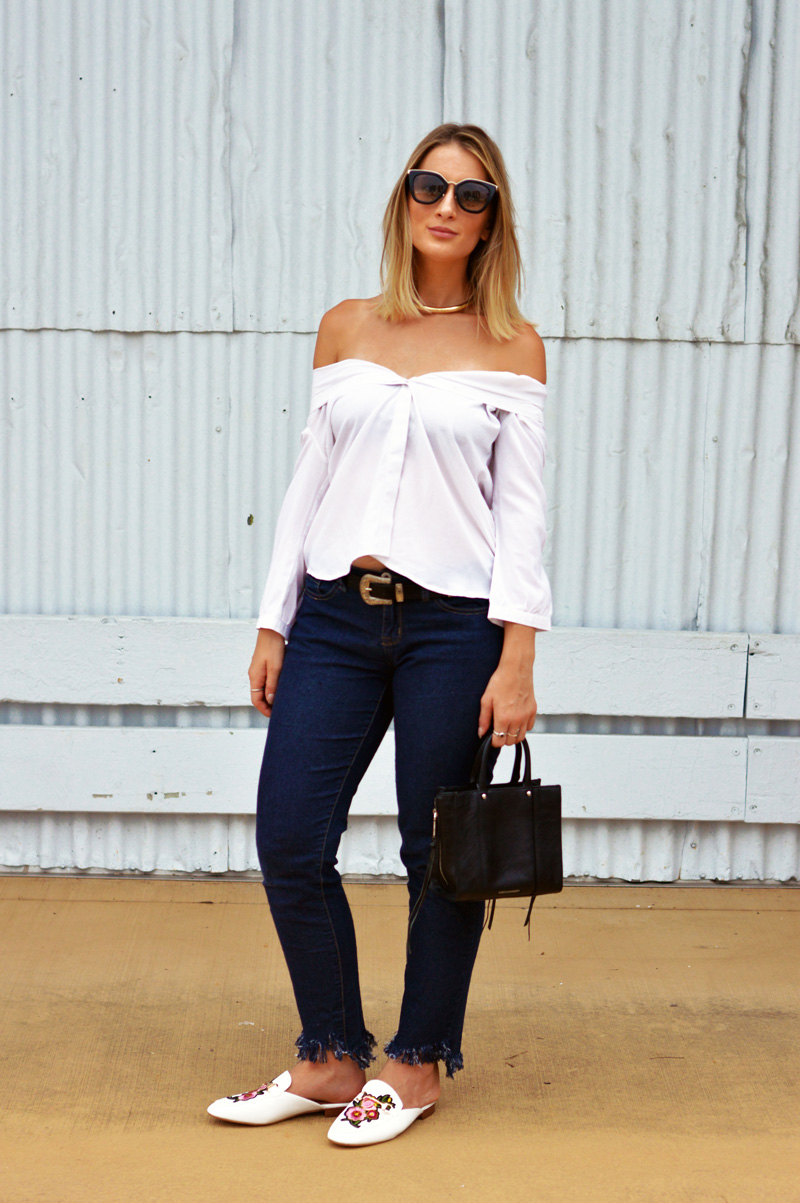 australian street style outfit blonde blogger wearing white blouse as off shoulder top fringe hem jeans embroidered floral loafers