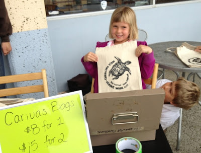 children selling canvas bags as fundraising for environmental program