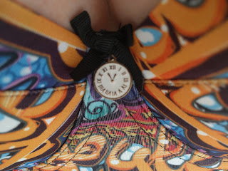 Close up on the clock shaped charm on the Graffiti's gore