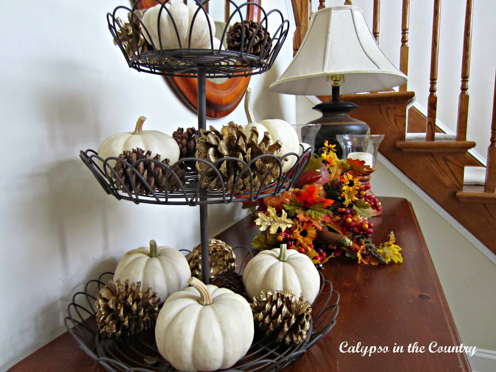Tiered stand with white pumpkins and pine cones