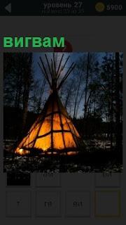 В темном лесу в ночное время установлен вигвам, в котором светится огонь и идет дымок