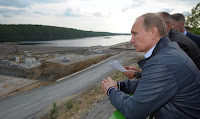 Russian president Vladimir Putin surveys the construction of a hydroelectric facility in Eastern Russia. (Photograph Credit: Alexey Druzhinin | Getty) Click to Enlarge.