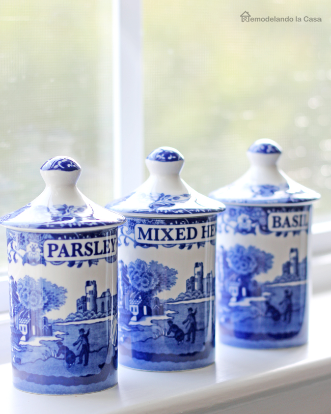 little white and blue condiment containers on kitchen window sill