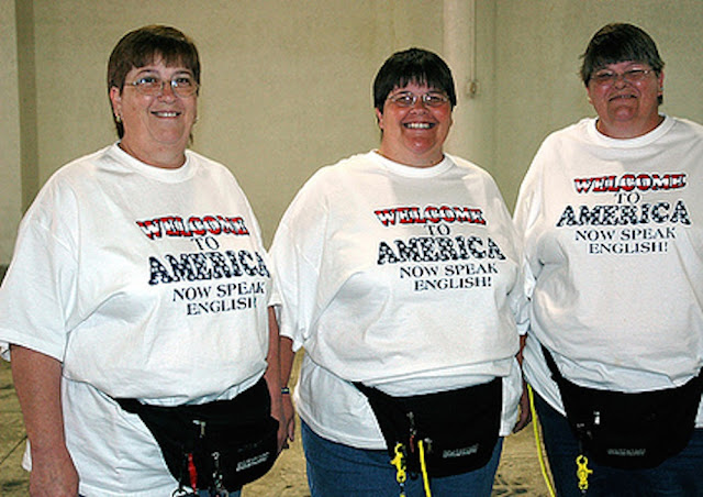 Three middle age, overweight, short-haired women wearing fanny packs and T Shirts. Welcome to America. Now Speak English. The Smell of Freedom and other stories about merica. marchmatron.com