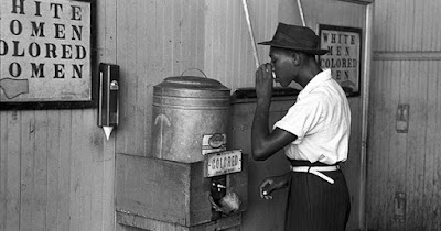Man drinking water during Jim Crow era