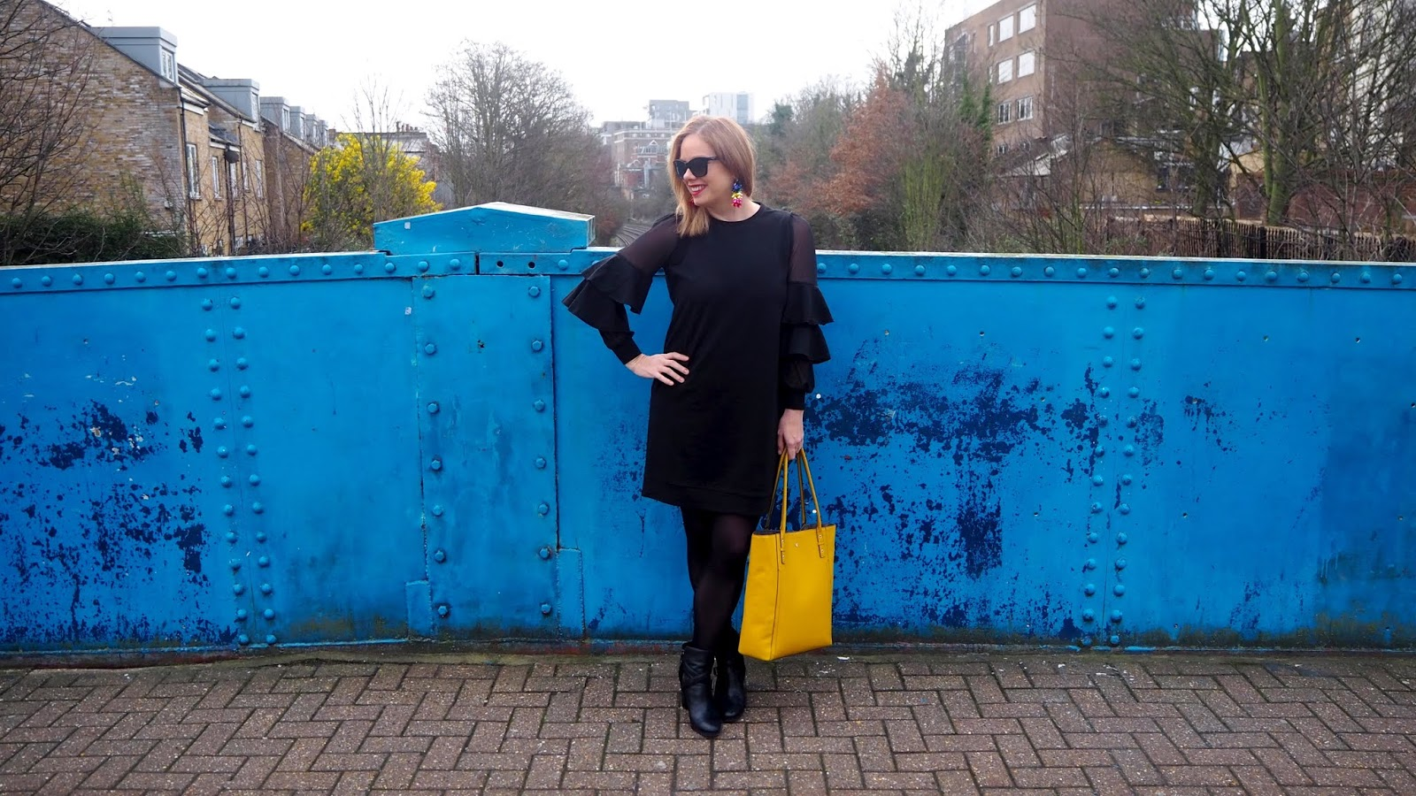 black sweat dress with ruffled sleeves and mesh, yellow bag, rainbow earrings