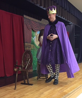 Man with purple cloat and crown walking across stage