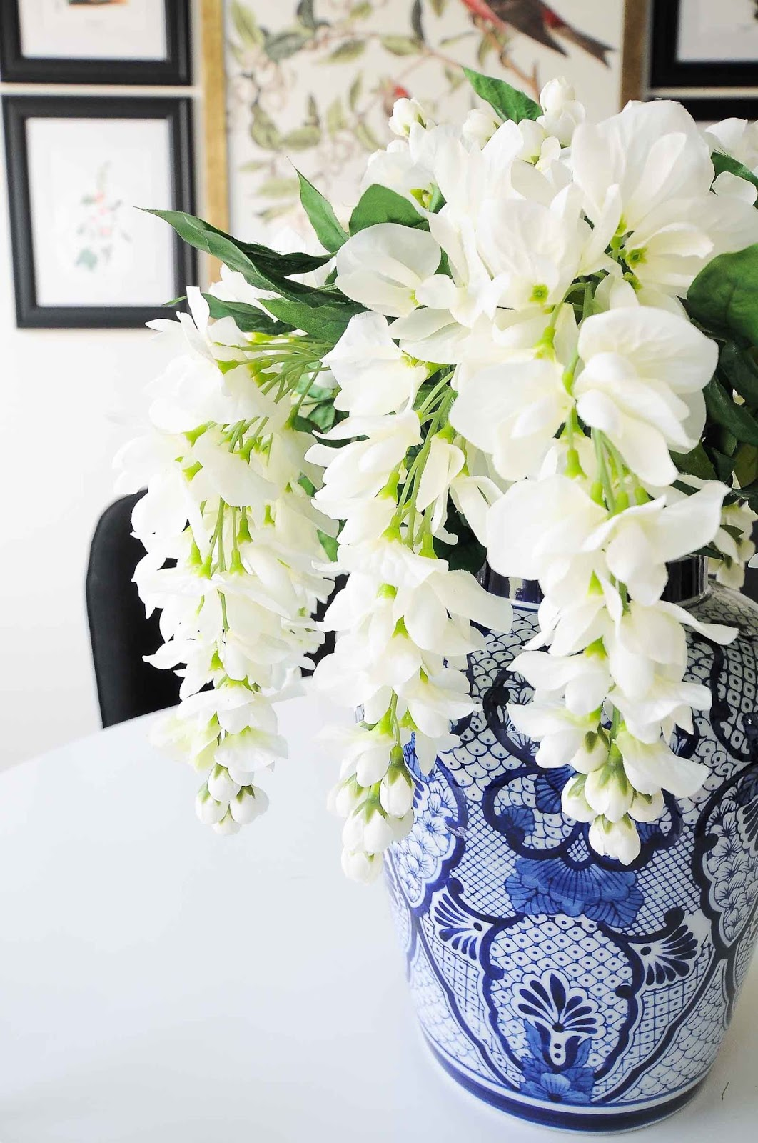 Gorgeous faux wisteria bushes in a ginger jar chinoiserie vase on a dining table.