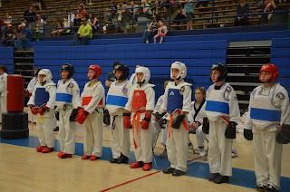 Martial arts kids lined up wearing sparring pads at a taekwondo tournament