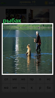 в воде стоит рыбак мужчина и ловит удочкой с собакой