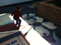Toddler dancing around a floor mural
