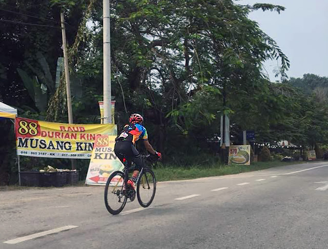 Cyclist passing the Durian stalls at Raub, Pahang