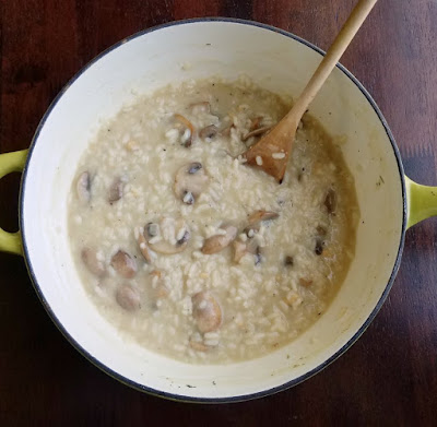 enameled cast iron pan with creamy rice and mushrooms in it... almost risotto
