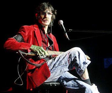 Foto de Charly García cantando con su guitarra
