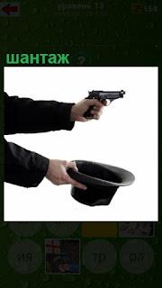 шантаж с пистолетом в одной руке и шляпа в другой