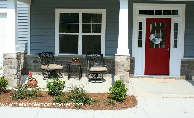 A front porch with a patio set in front