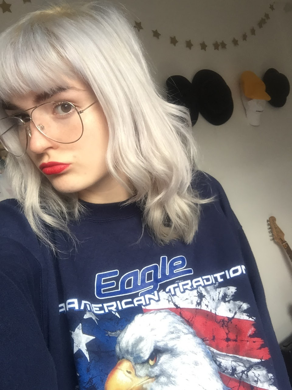 silver haired girl wearing vintage jumper, red lipstick and aviator glasses
