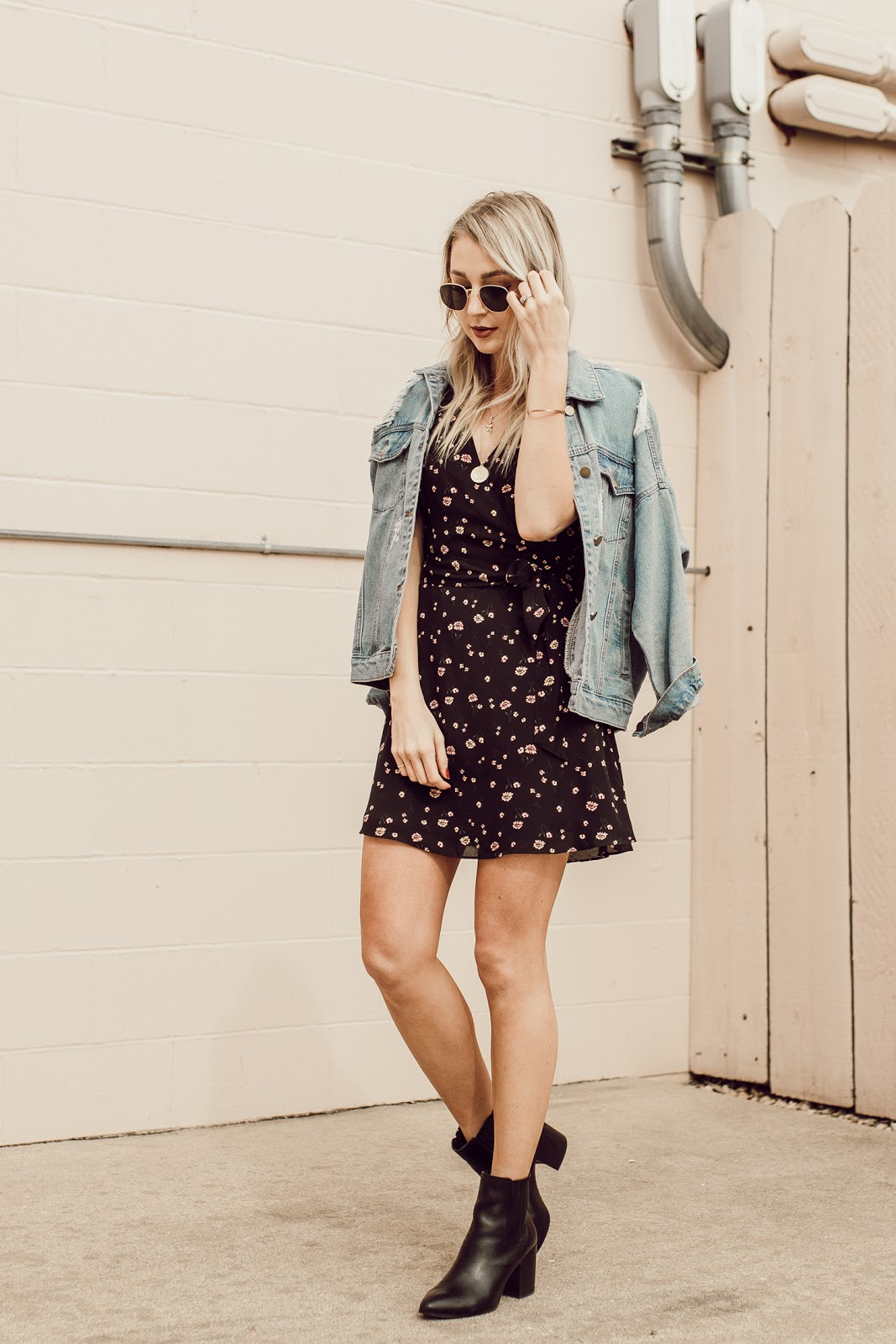 denim jacket over a floral wrap dress