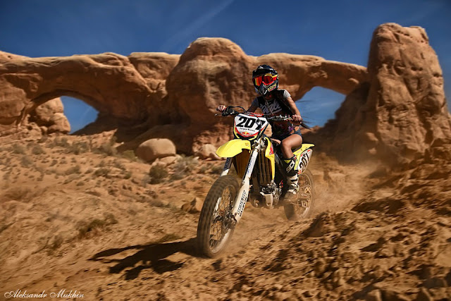 Girl rides a Suzuki dirt bike in the desert wearing shorts, MX helmet and goggles and MX boots