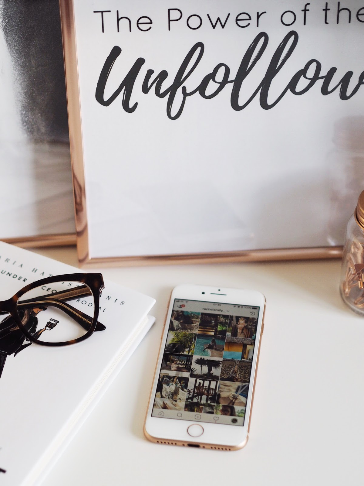 iphone 8 with RachelEmily__ instagram, glasses and the power of the unfollow poster in copper frame