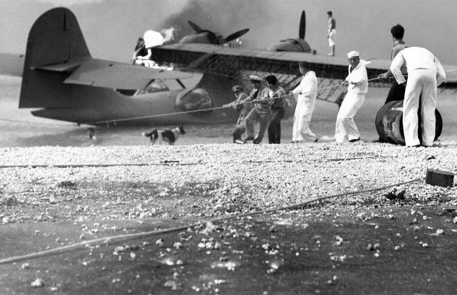 Sailors at Naval Air Station (NAS) Kaneohe attempt to salvage a burning PBY Catalina in the aftermath of the Japanese attack on Pearl Harbor.