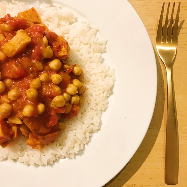 Rice on plate topped with sweet potato and chickpea curry, gold cutlery to right side