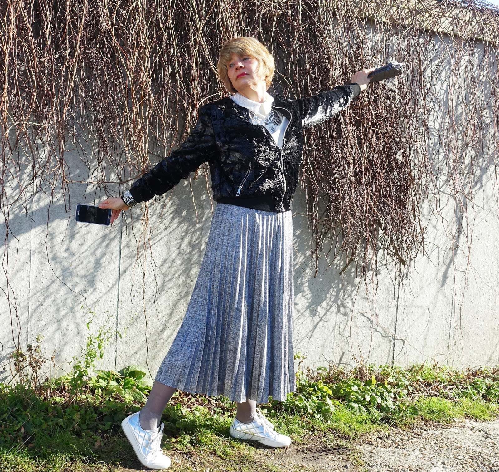 Image showing a woman in midi length metallic pleated skirt, black sequinned bomber jacket and silver Edie shoes by Vionic