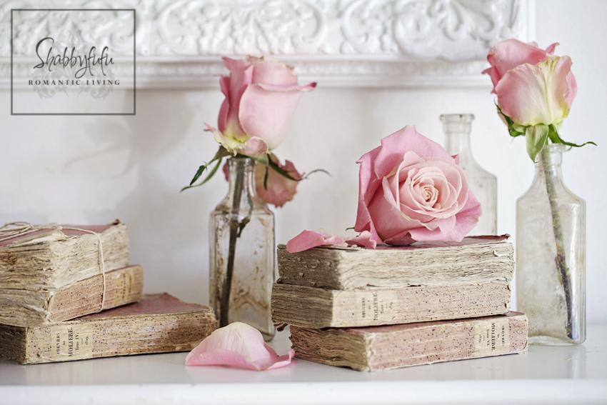 romantic room designs - blush pink roses displayed on vintage books on a bedroom mantel
