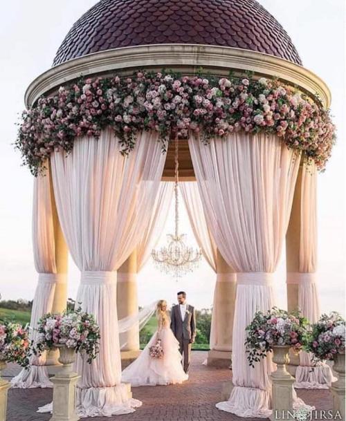 Casal de noivos num cenário decorado com flores e véus.