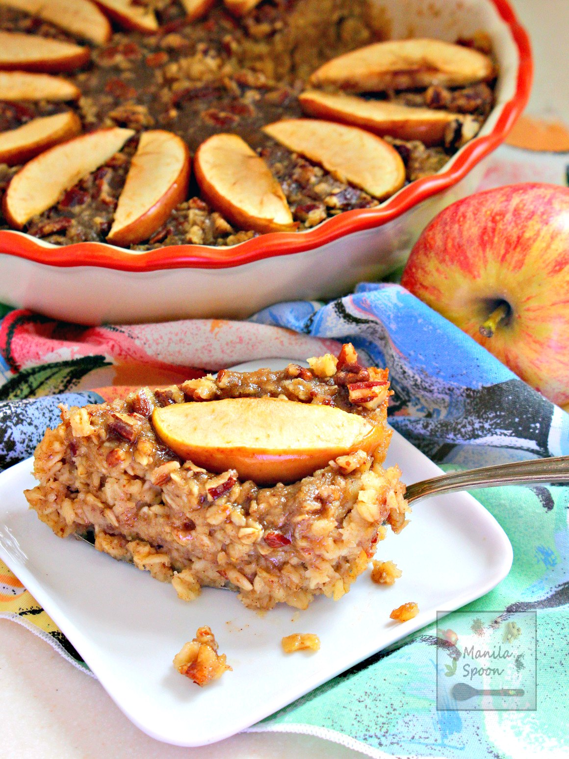 Cinnamon flavored oatmeal with apples and a buttery, crunchy praline topping is a delicious fall or winter breakfast or brunch dish! | manilaspoon.com