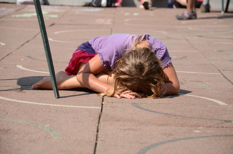 Girl (child) lying on a playground crying