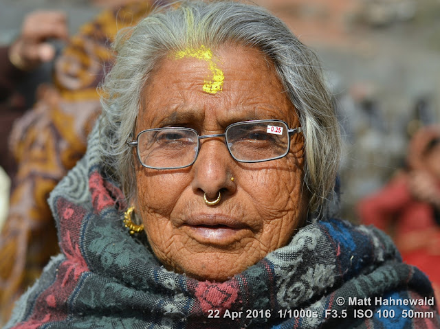 shakti peetha; Muktinath; Muktinath Temple; Hindu; puja; pilgrim; old Indian woman; yellow tilaka; blanket; reading glasses; Matt Hahnewald Photography; Facing the World; photo; image; closeup; street portrait; head shot; outdoor; world cultures; cultural; one person; character; people; female; adult; ethnic; horizontal; human; face; eyes; eye contact; photography; consent; empathy; rapport; portrait; portraiture; environmental portrait; ethnic portrait; travel portrait; color; 4x3; Mustang District; posing; Asia; South Asia; Nepal; Himalayas; Annapurna Circuit; Nikon D3100; Nikkor AF-S 50mm f/1.8G; trekking; colorful; en face; front view; incredible; wrinkles; lived-in face; depth of field; bokeh; nose ring; nose jewelry; religion; Hinduism; bareheaded