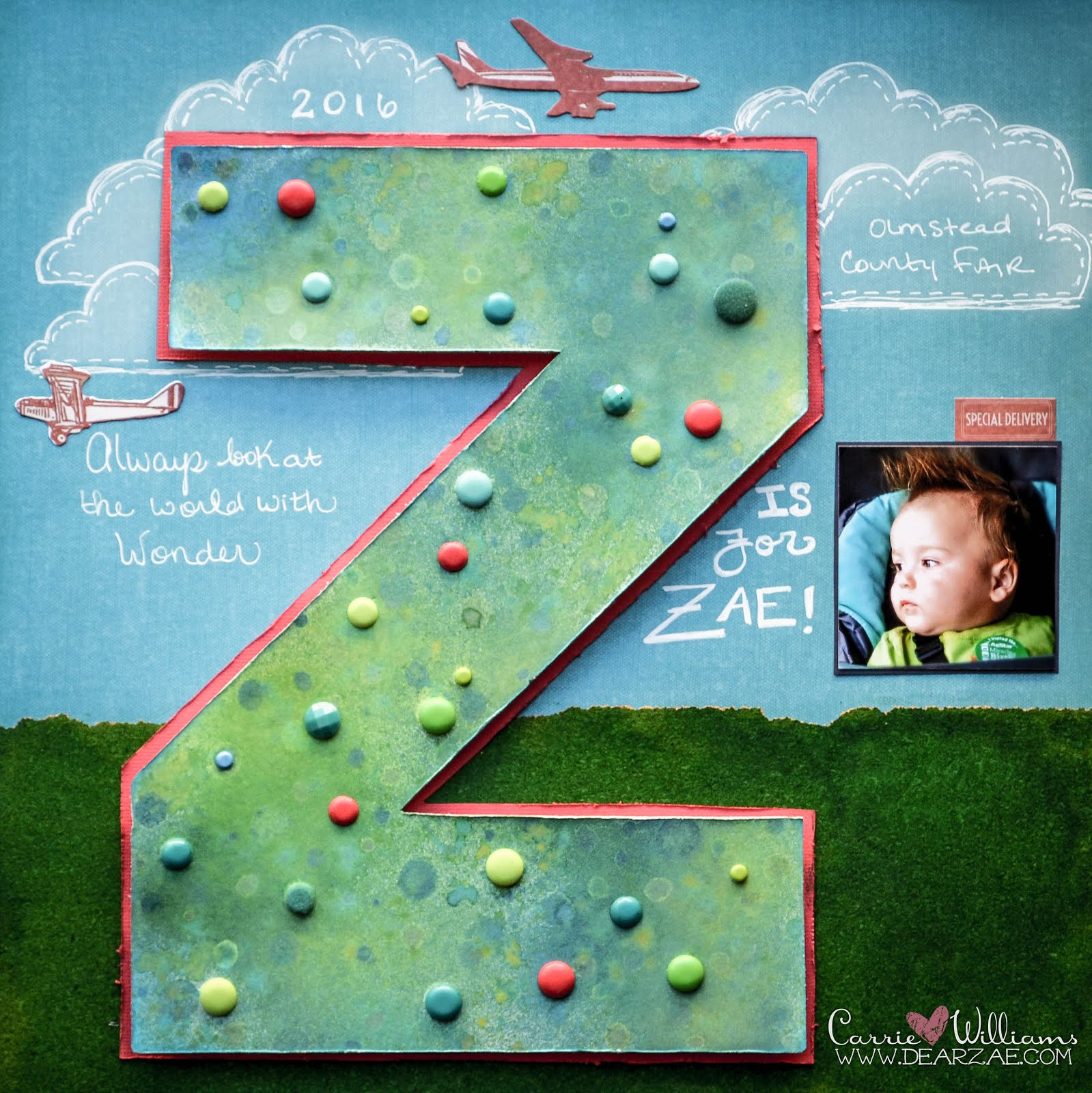 Boy scrapbooking page layout with large watercolor letter Z decorated with brads against blue sky background and cork grass and airplanes and hand drawn clouds