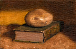 Oil painting of a white potato on top of a green linen-bound book.