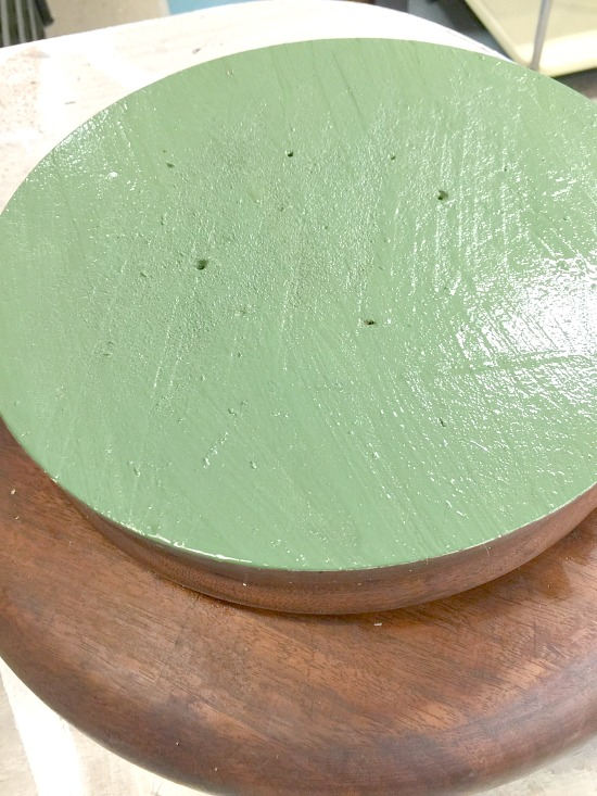 a wooden lazy susan with a painted green bottom