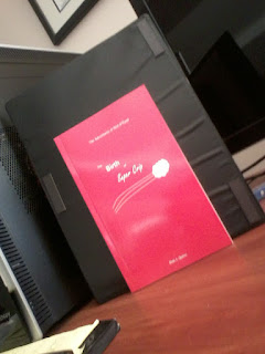 The book propped up on my desk, front cover showing