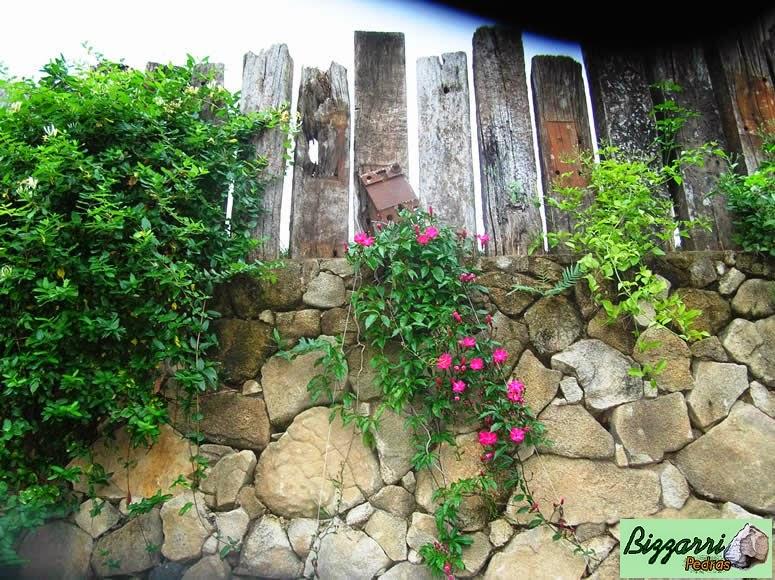Detalhe do muro de pedra com a fixação dos dormentes de madeira e o detalhe da execução do paisagismo encorporando as plantas madressilva com os dormentes.