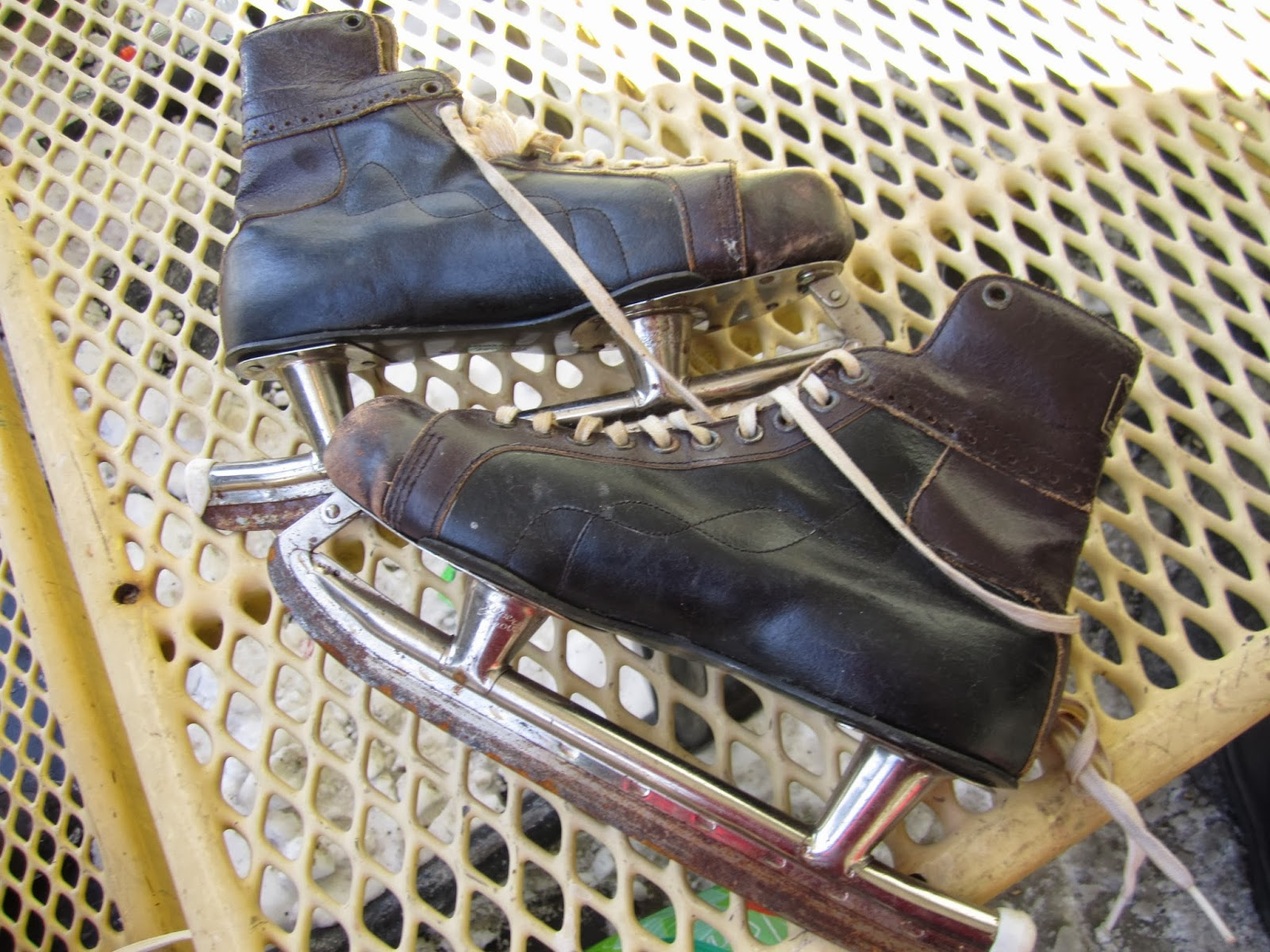 A pair of black leather ice skates that look very old