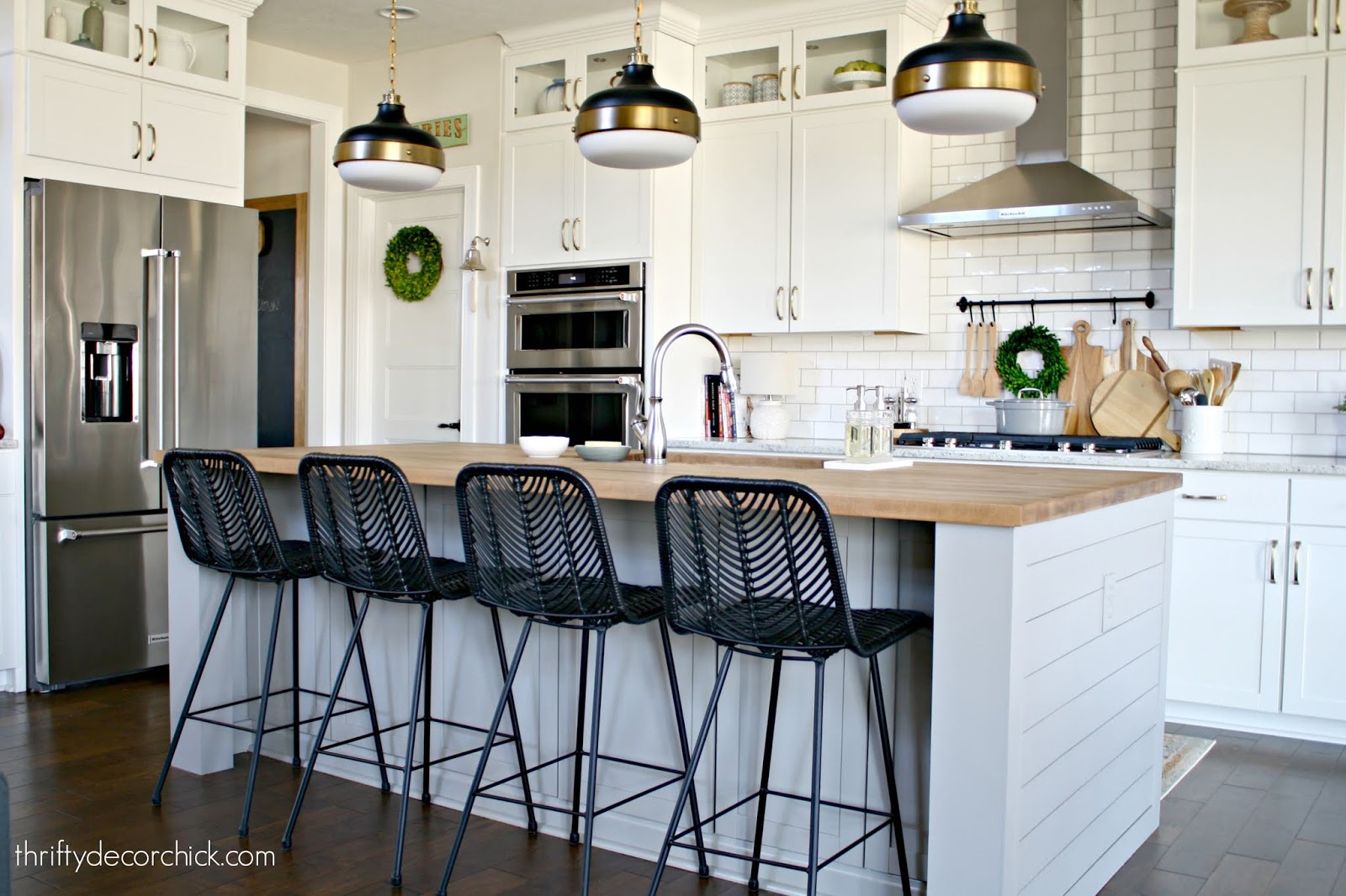 Gray island black stools white kitchen
