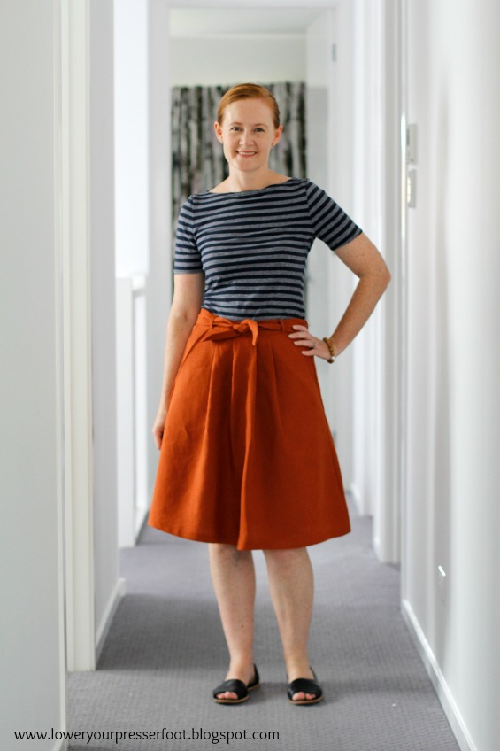 lady wearing a rust coloured pleated skirt and blue and white stripe tshirt
