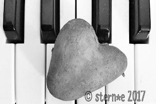 Klaviertasten mit Herzkartoffel in Grautönen
