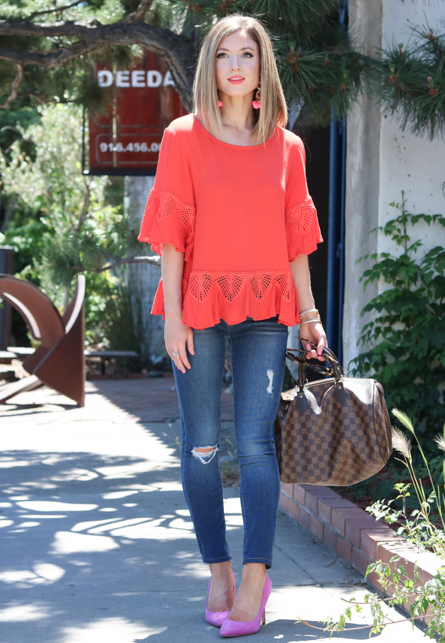 Orange shirt and pink pom earrings.