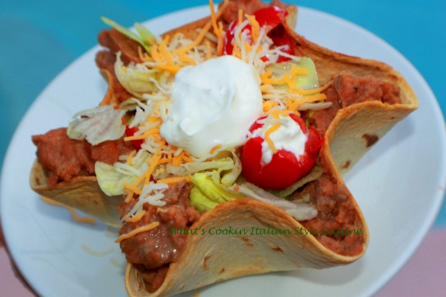 this is a taco flour tortilla bowl filled with salad ingredients like shredded lettuce, tomatoes, shredded cheese, ground beef, topped with sour cream  and taco sauce on top or salsa