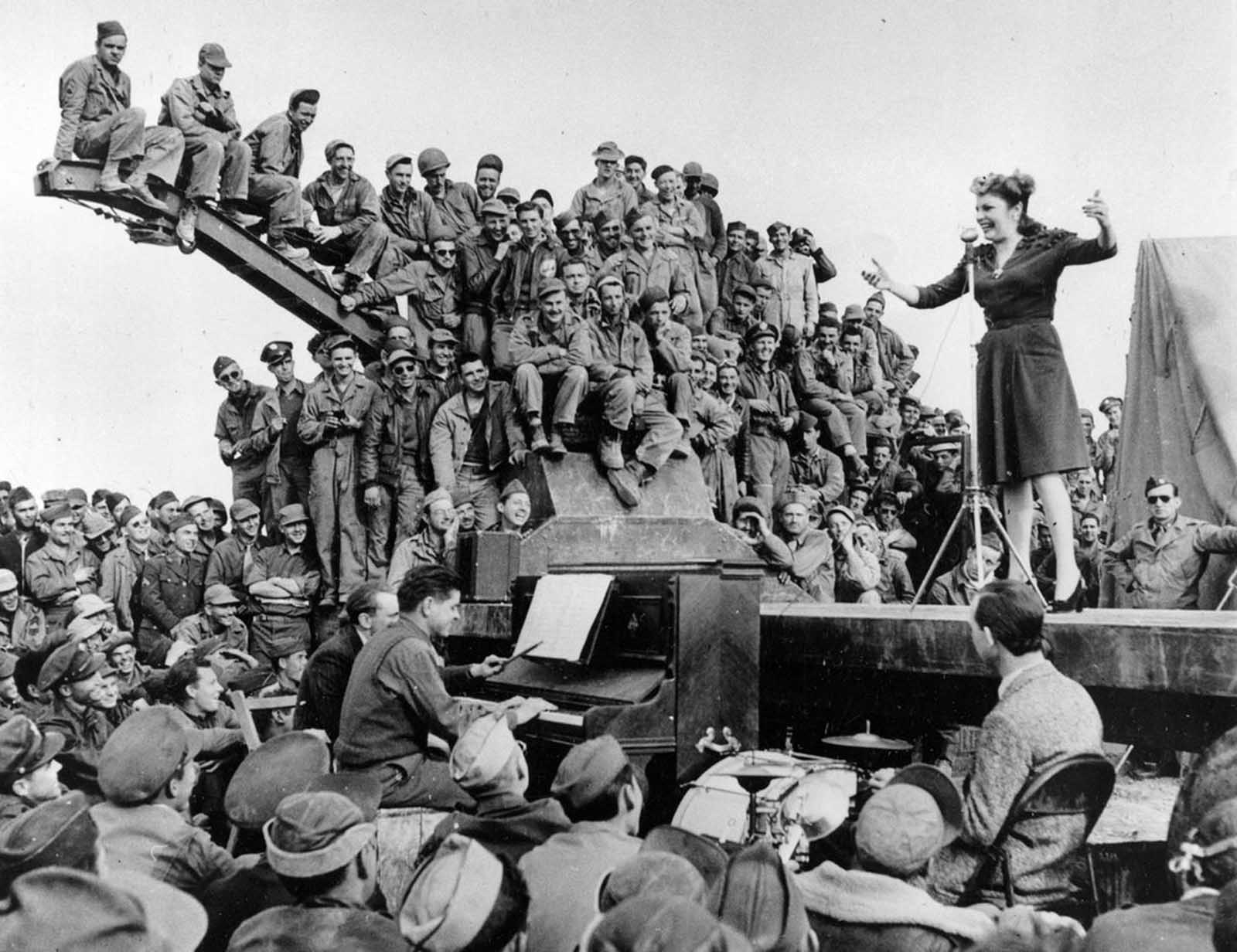 Actress-comedian Martha Raye entertains servicemen of the U.S. Army 12th Air Force on a makeshift stage on the edge of the Sahara Desert in North Africa in 1943.