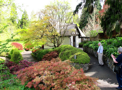 Two people admiring an english-style garden in front of an arts-and-crafts-style cottage.