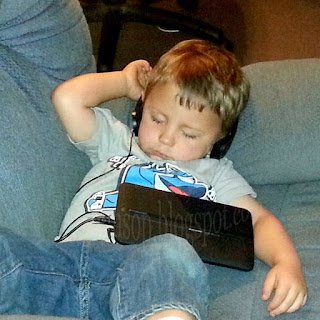 grandson benjamin fast asleep in a recliner wearing headphones with a taplet lying on his stomach