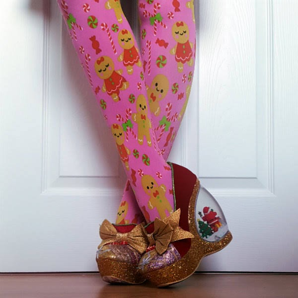 crossed legs showing red velvet inner side of shoe with gold bow and glitter parcel front